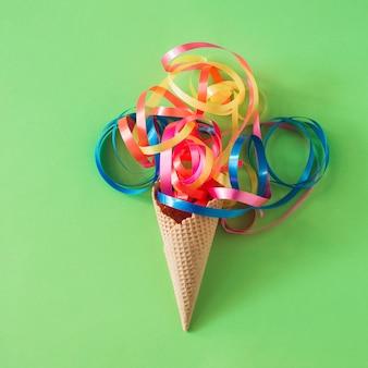 緑の背景にワッフルアイスクリームコーンの上にカラフルなリボン