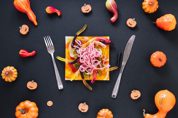 Декоративная еда хэллоуина, окруженная тыквами