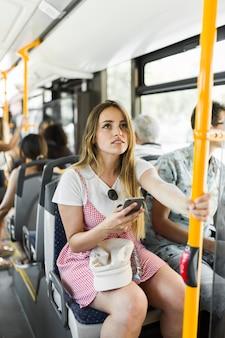 バスに乗っている若い女性