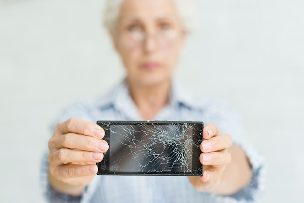 亀裂のあるスクリーンでスマートフォンを表示しているシニアの女性