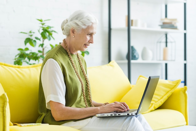 Улыбается молодая женщина, сидя на желтый диван, используя ноутбук