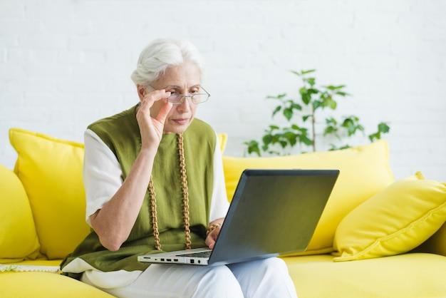 ラップトップを見る黄色のソファに座っている高齢者の女性