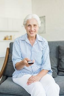 Улыбаясь старший женщина, сидя на диване с помощью дистанционного управления