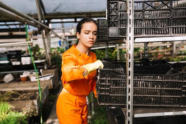 若い女性の庭師ラックからクレートを削除する