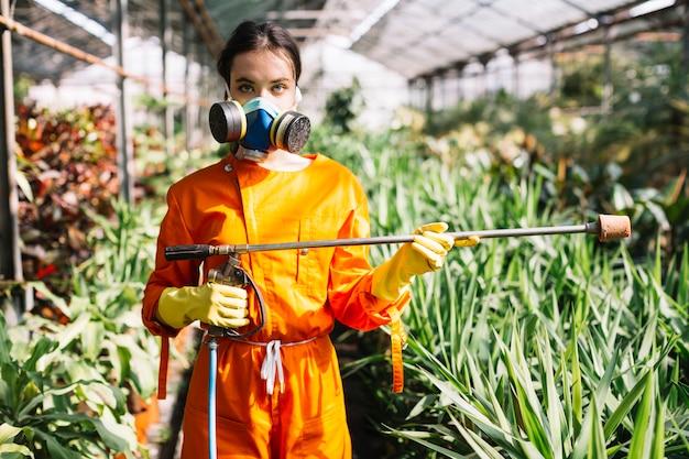 温室で噴霧器を持っている女性の庭師の肖像