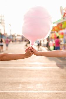 綿のキャンディーを手に持つ手