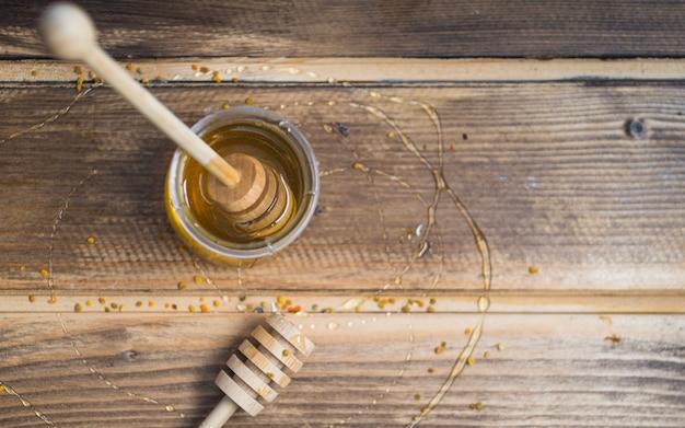 Медовый горшок и пыльца пчел на деревянном столе