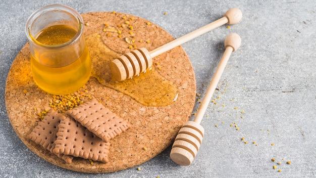 Горшок меда; печенье; деревянный медовый ковш и пыльца пчел на бетонном фоне