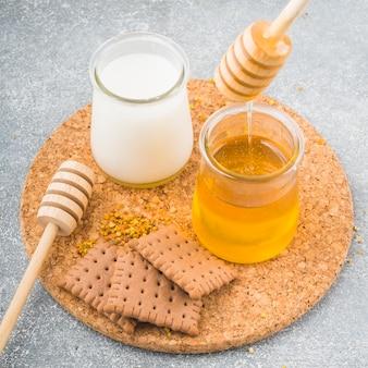 ミルクとハニーポットコルクコースターを持つビスケットとミツバチの花粉