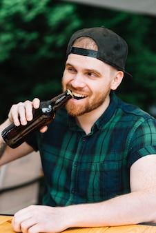 彼の歯でビール瓶の帽子を開けている男
