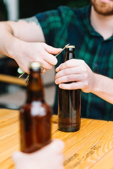 木製のテーブルにオープナー付きのボトルを開く男のクローズアップ
