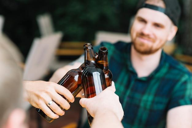 友人とビールのガラス瓶をたたく男