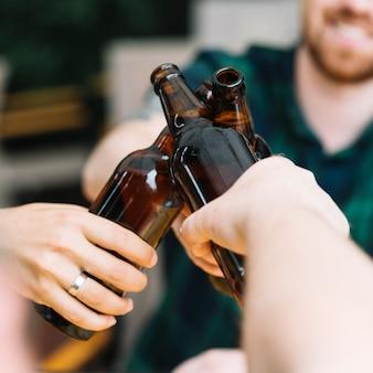 茶色のビール瓶をしゃがむ友人のグループ