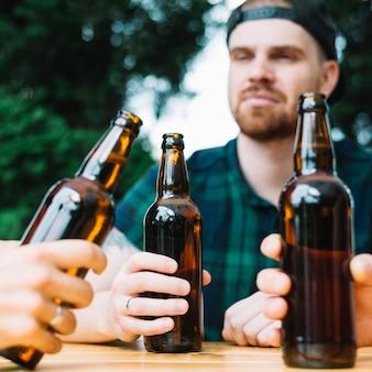 彼の友人と飲み物を楽しんでいる男