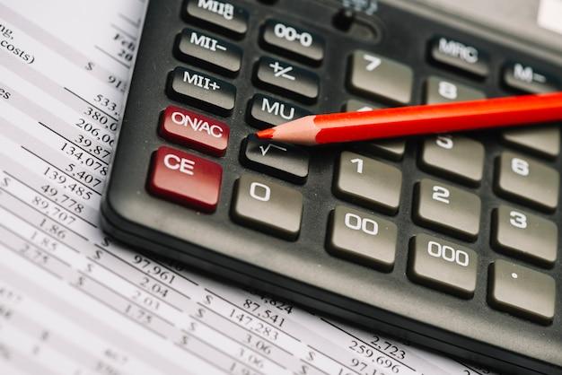 Красный цветной карандаш на калькуляторе над финансовым отчетом