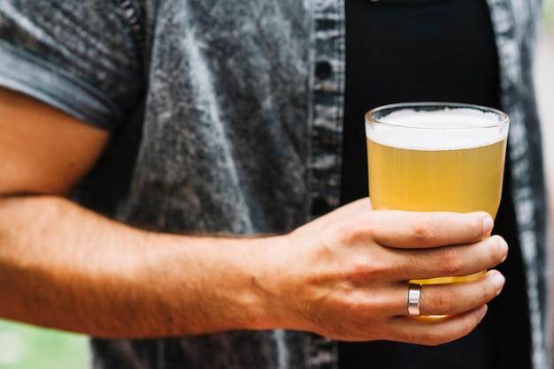 Крупным планом человек, держащий стакан пива
