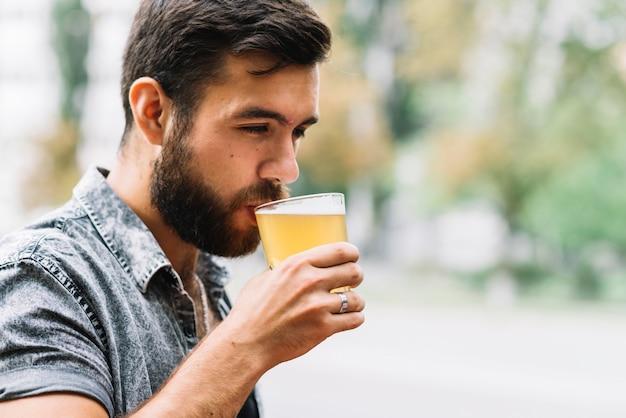 屋外でビールのガラスを飲む男のクローズアップ