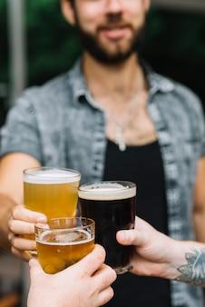 彼の友人とビールの眼鏡を応援する男のクローズアップ