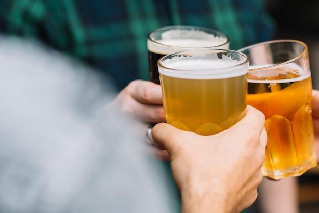 ビールのガラスで応援する友人の手のグループ