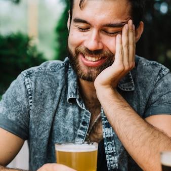 Крупным планом улыбающегося человека, держащего стакан пива