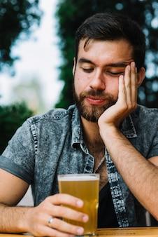 ビールのガラスを持っている眠そうな男