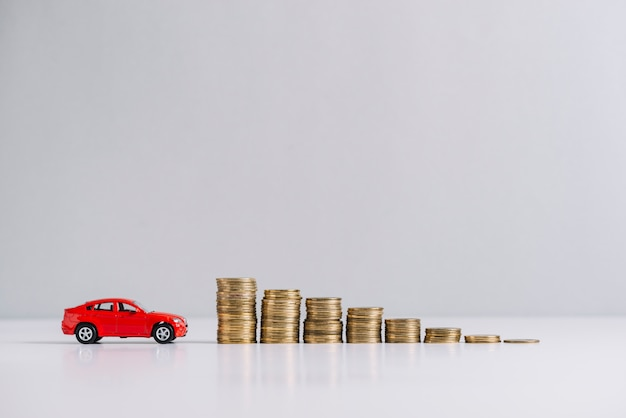 積み重ねた硬貨の近くに赤い車