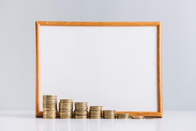 反射的な机の上の空白の白いボードの前に積み重なったコインを増やす