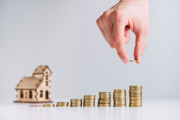 家のモデルの前にコインを積み重ねる人の手