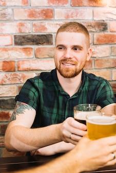 幸せな男はバーでアルコールのメガネを焼く