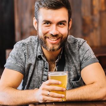 ビールのガラスを持っている幸せな男