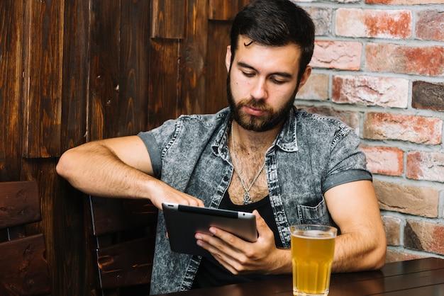 テーブル、ビール、デジタルタブレットを使用している男