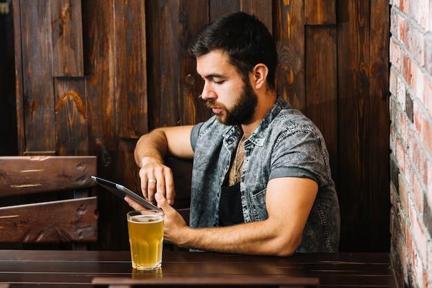 デジタルタブレットを使用してビールのガラスを持つ男