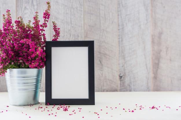 白いフォトフレームとピンクの花をアルミポットに入れて机に