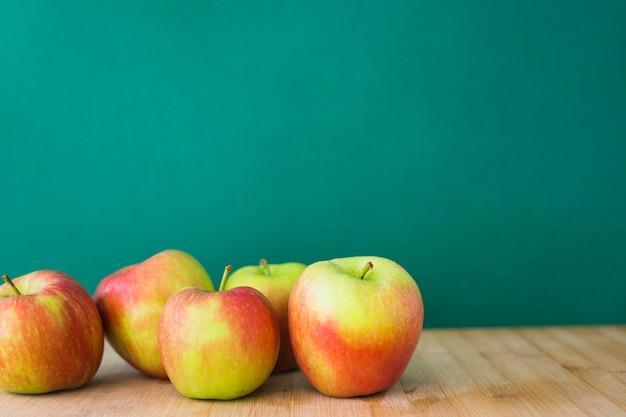 緑の背景に木製のテーブルにリンゴ