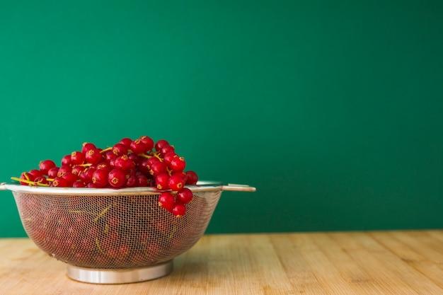 緑色の背景に木製の机の上のストレーナーで新鮮な赤いカラントの果実
