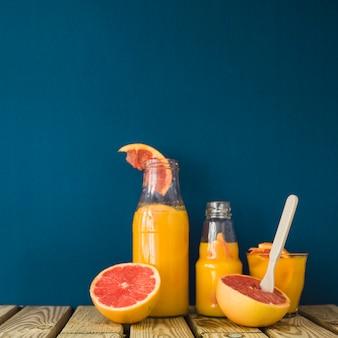 Спелые грейпфруты со стеклом и бутылками сока на деревянном столе