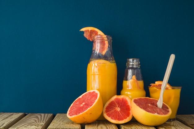 青色の背景のテーブルにジュースを半分にしたグレープフルーツ