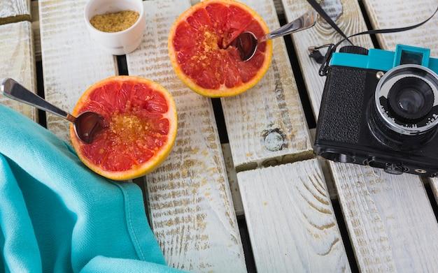 Старинная камера и салфетка с половинным грейпфрутом на деревянном фоне