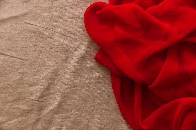 茶色のファブリックの背景に滑らかな赤い織物