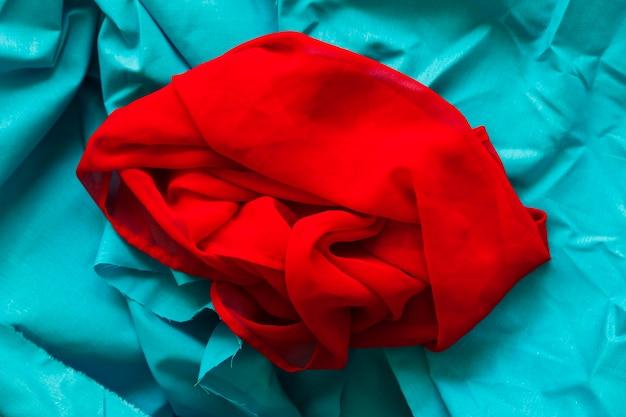 ターコイズ布の背景に滑らかな赤い織物