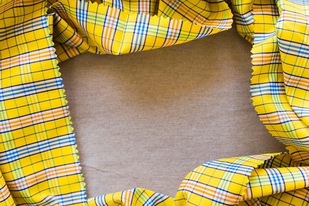 黄色のチェッカーパターンのテーブルクロスフォーミングフレームの高い角度のビュー