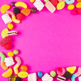 ピンクの背景に様々な形の甘いキャンディー
