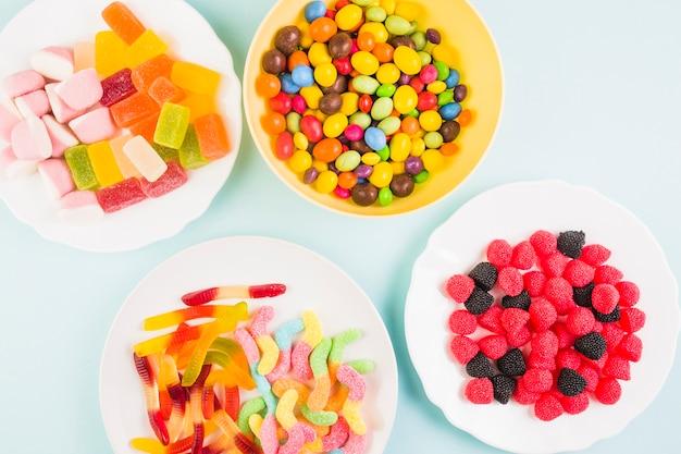 色とりどりの背景の上にプレート上の様々な甘いキャンディーの上昇したビュー