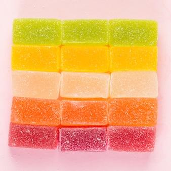 ピンク色の表面に四角形を形成するカラフルなゼリーのキャンデー