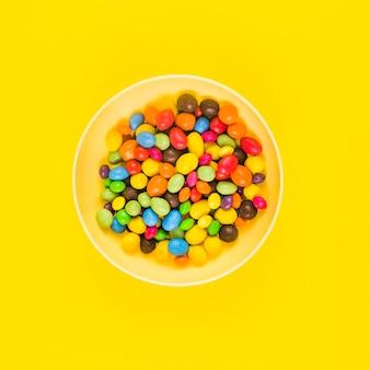 黄色の表面上のプレートにカラフルな甘いキャンディーの高い角度のビュー