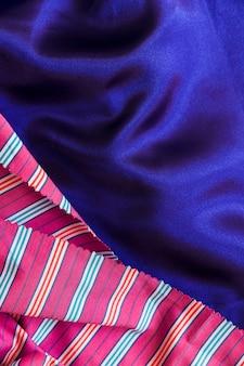 滑らかな青の布の上に縞模様の織物のクローズアップ
