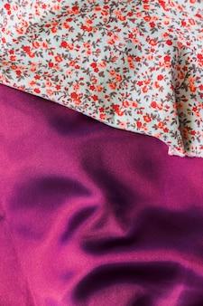 Крупным планом текстиль цветочного рисунка на гладкой фиолетовой ткани