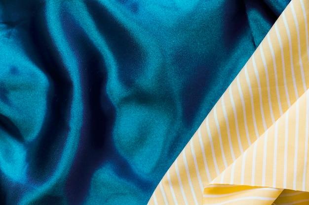 青い織物の背景に黄色の縞模様