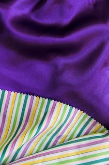 Красочная полосатая полосатая ткань на гладком фиолетовом текстиле