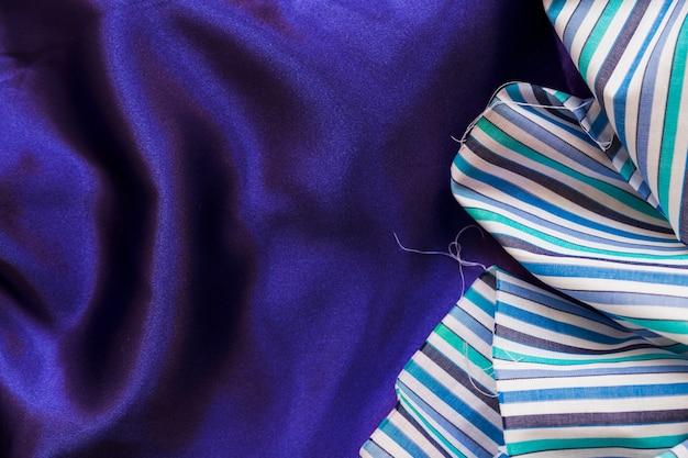Повышенный вид красочного тканевого материала на гладкий фиолетовый текстиль